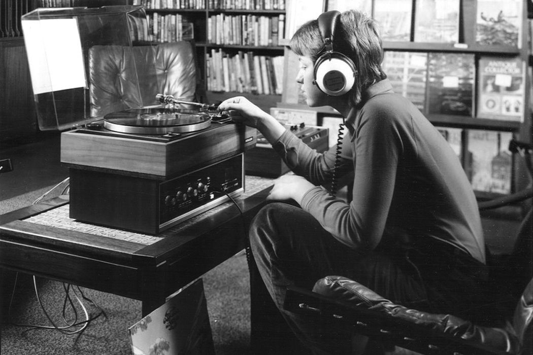 A teenager listening to a record through headphones