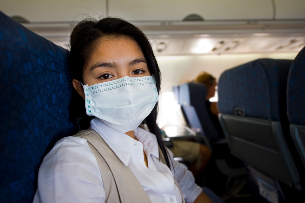 A woman with a protective mask in a plane