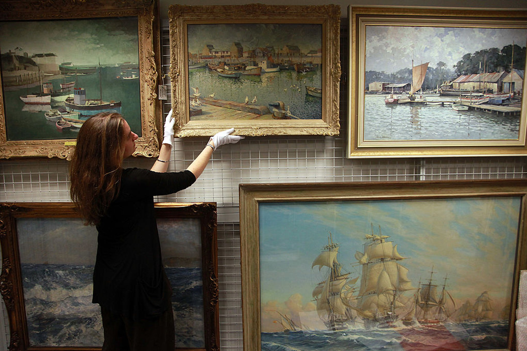 An assistant curator at the National Maritime Museum Cornwall inspects a rare painting that is currently being kept at the museum store and warehouse