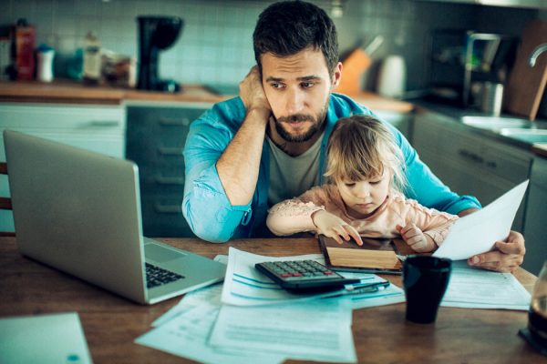 A man with his daughter paying a bill