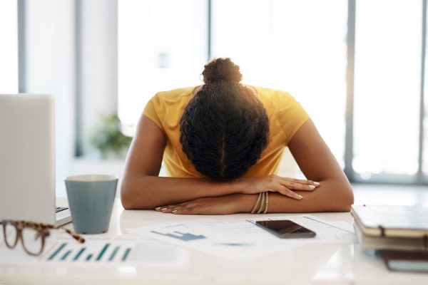 A woman resting her head on her work desk