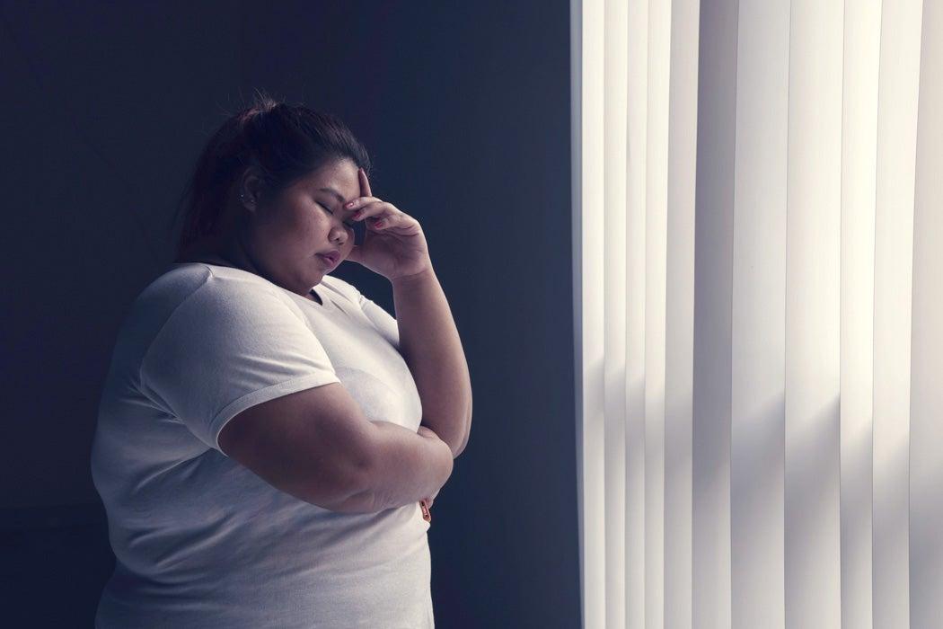 A woman in pain, standing beside a window