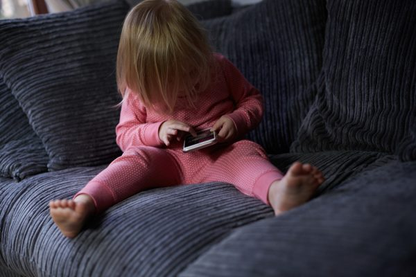 A young girl using a cell phone while sitting on a couch.