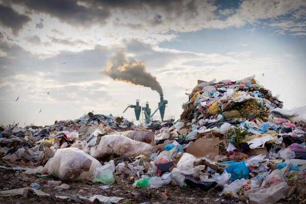 A landfill with smoke in the background