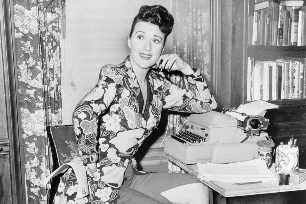 Gypsy Rose Lee seated at a typewriter