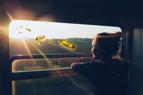 A woman looking out a train window into the sunset with vitamin d pills approaching