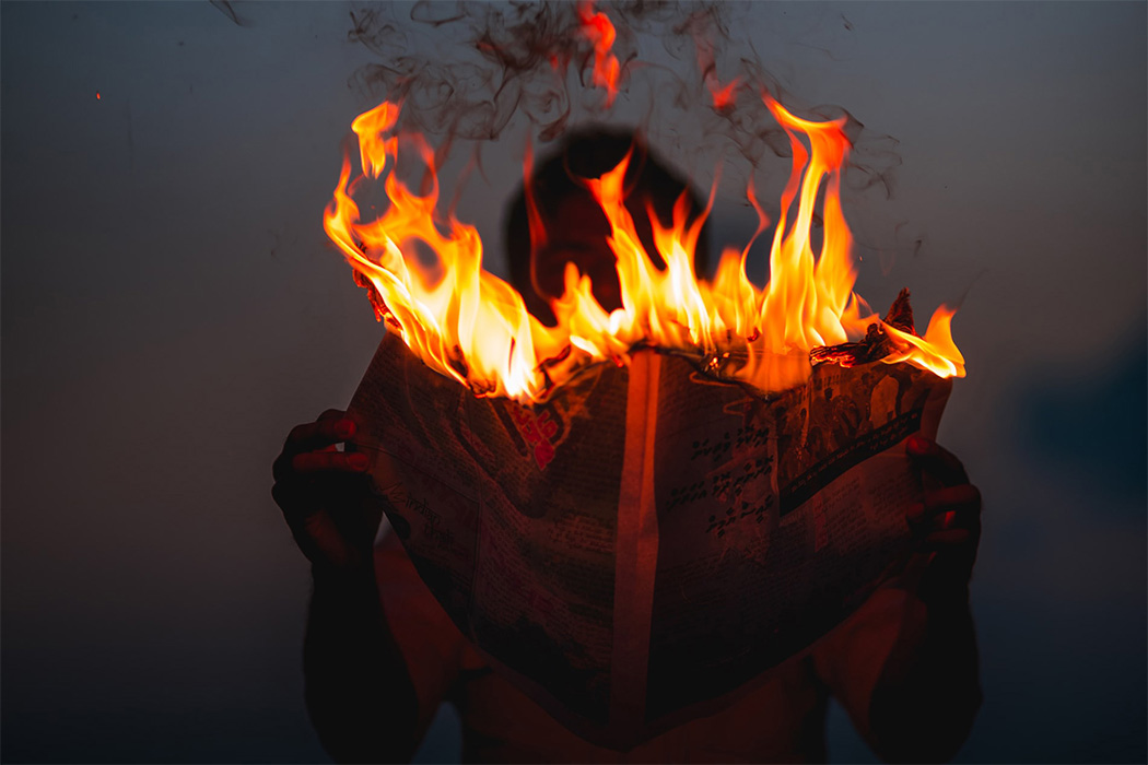 A person holding a newspaper on fire
