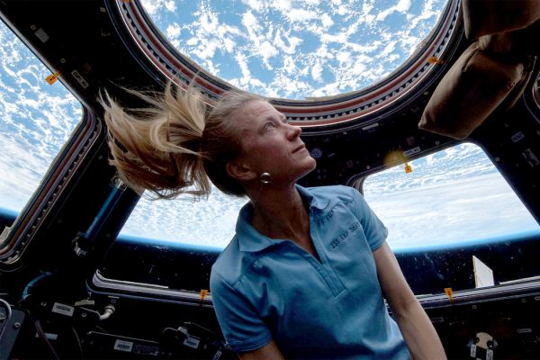 Astronaut Karen Nyberg looks at Earth through a cupola on the ISS.