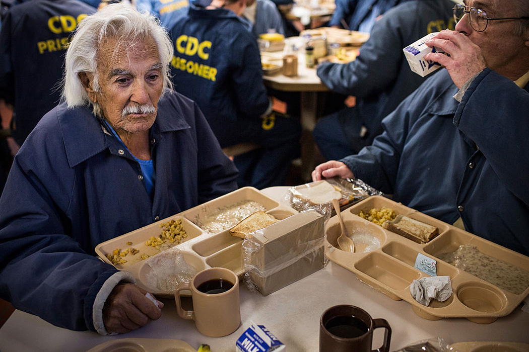 Anthony Alvarez (L), age 82, eats breakfast with Phillip Burdick, a fellow prisoner and member of the Gold Coats program at California Men's Colony prison on December 19, 2013 in San Luis Obispo, California.