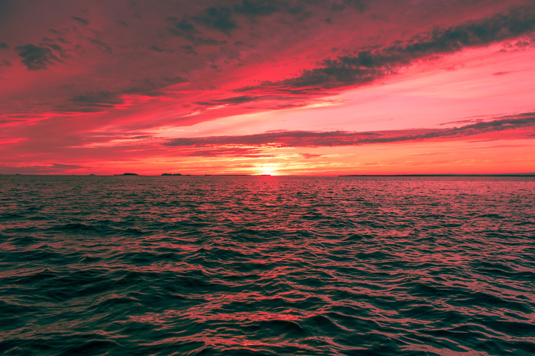 A sunset on the ocean with a red sky