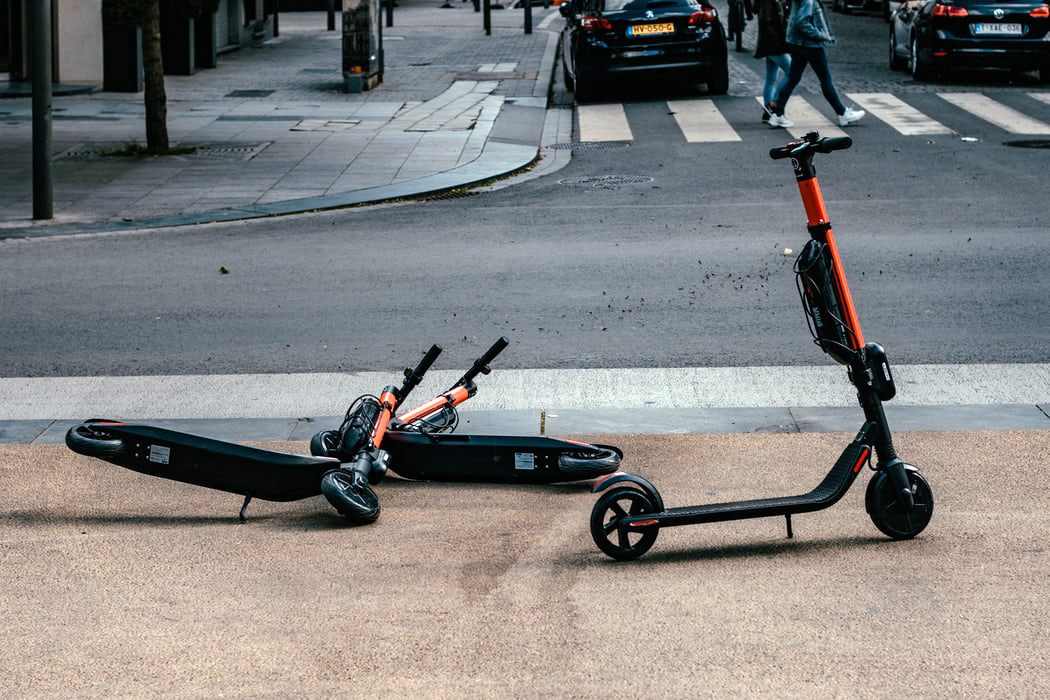 Scooters lying on a sidewalk