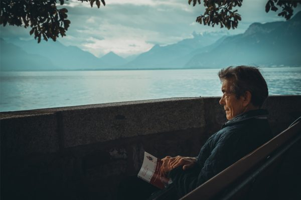 An elderly man sitting beside a lake