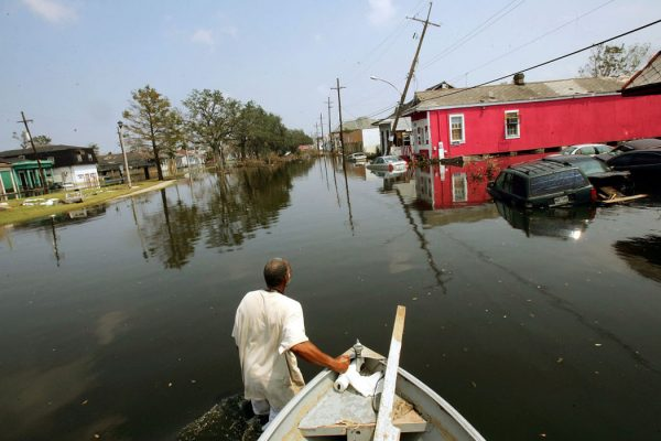 Ira Jackson pulls his boat through a flooded street September 5, 2005 in New Orleans, Louisiana after Hurricane Katrina