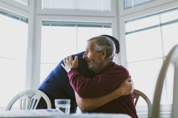 Caretaker embracing senior man at home