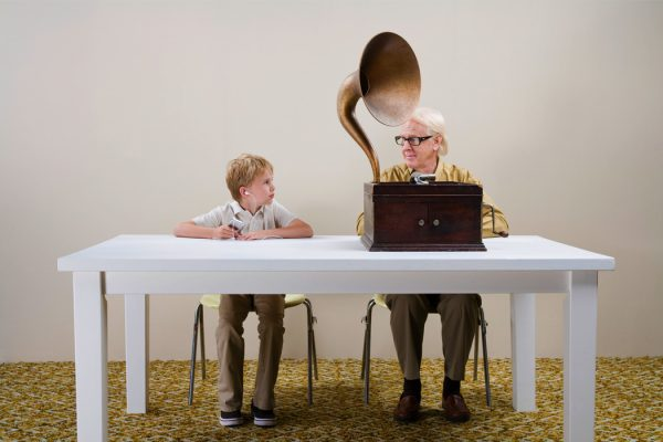 A child and old man sitting at a table with their respective music technologies