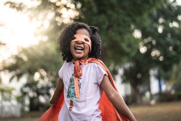 A little girl playing superhero