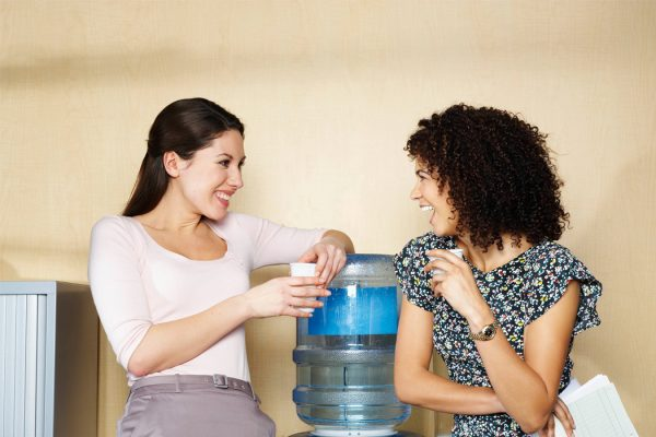 Two women speaking beside a water cooler in an office