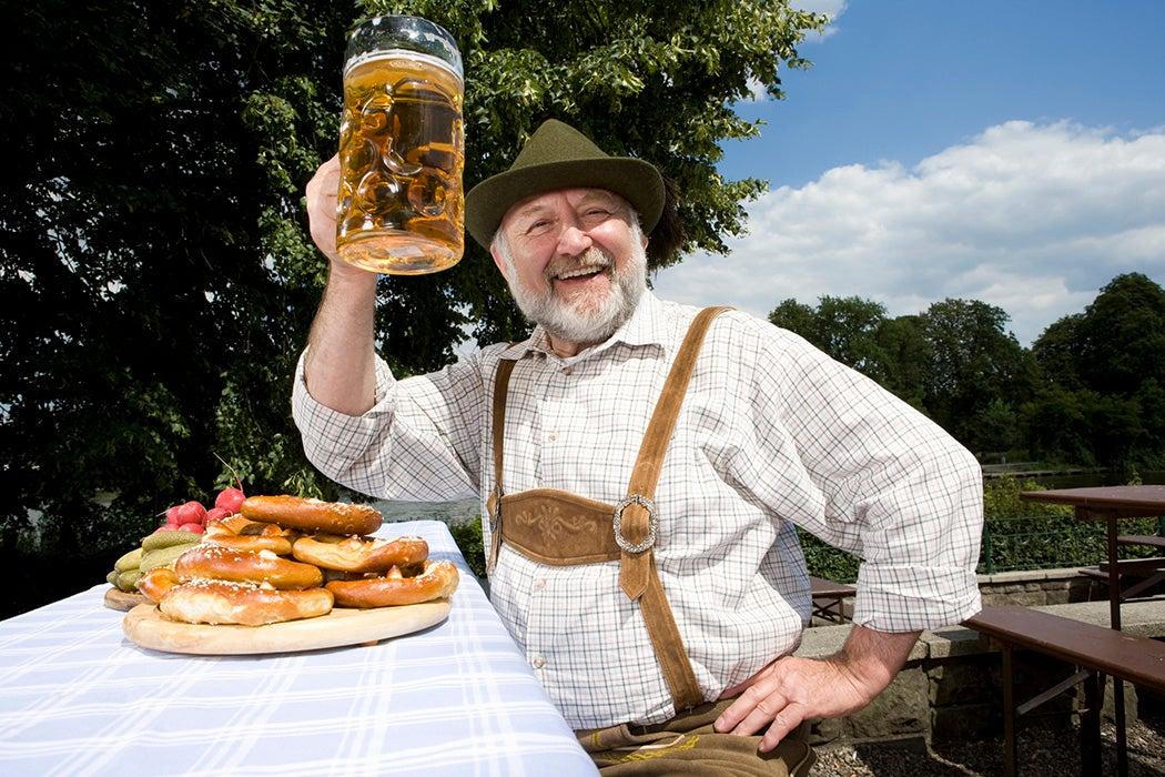 A German man in lederhosen holding a beer stein