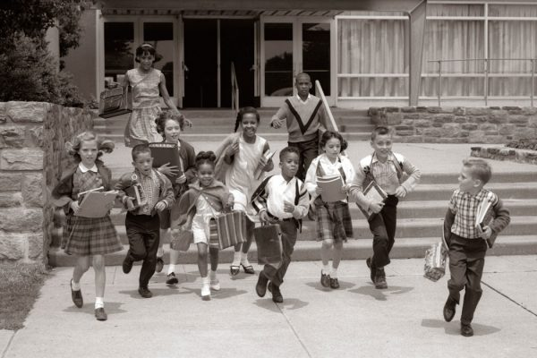 Circa 1960s: Group Of Grade School Children Running Down School Stairs With Books & Bags.