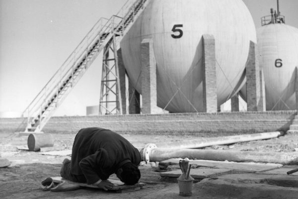 Photograph: A Mohammadan praying towards Mecca when the Miezzin calls from a nearby mosque, with a Butane Gas reservoir in the background. circa 1950