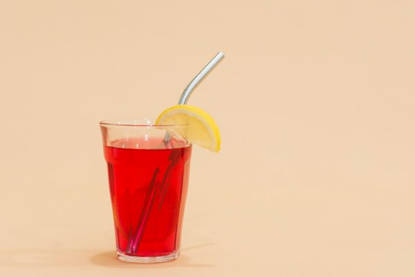 A red drink in a glass with a metal straw