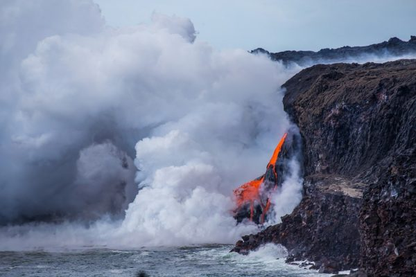 A new lava stream cascades into the ocean at the former lava delta site in Hawai'i Volcanoes National Park.