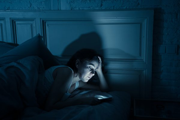 A woman looking at her phone in bed