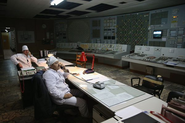 Workers sit in the control room of reactor number two inside the former Chernobyl nuclear power plant