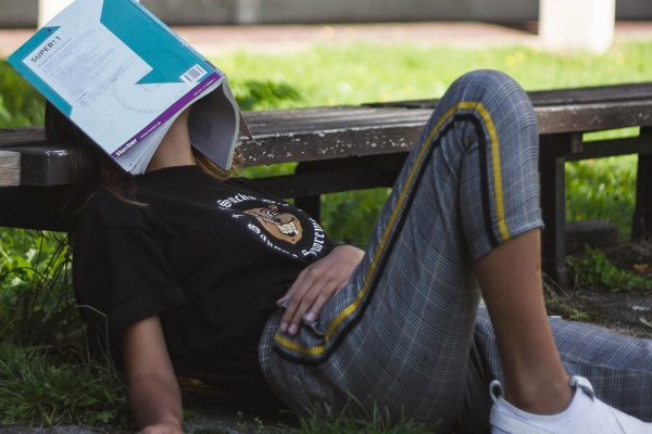 A person reclining with a book over their face