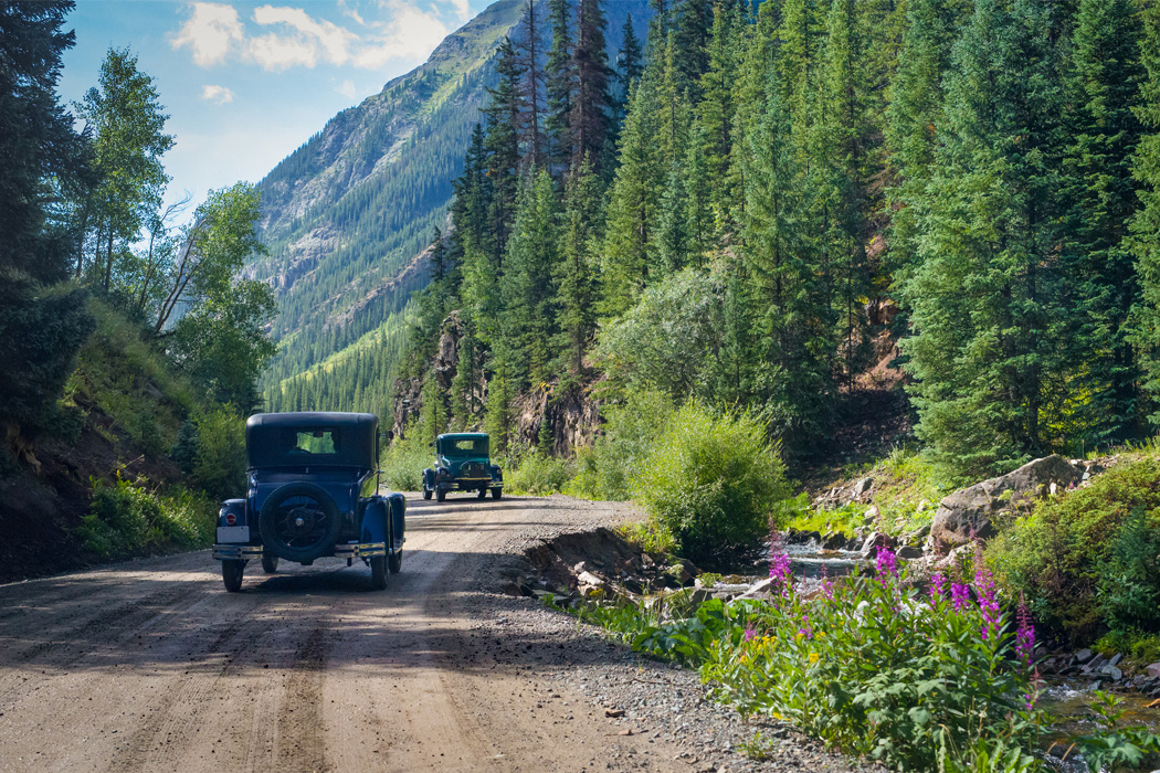 Classic cars drive along dirt road in the mountains