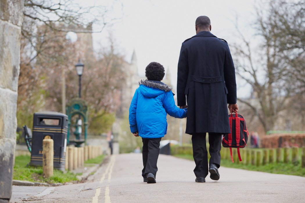 A father and his son walk to school