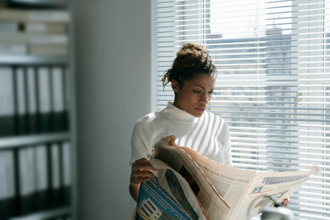 A woman reading a newspaper