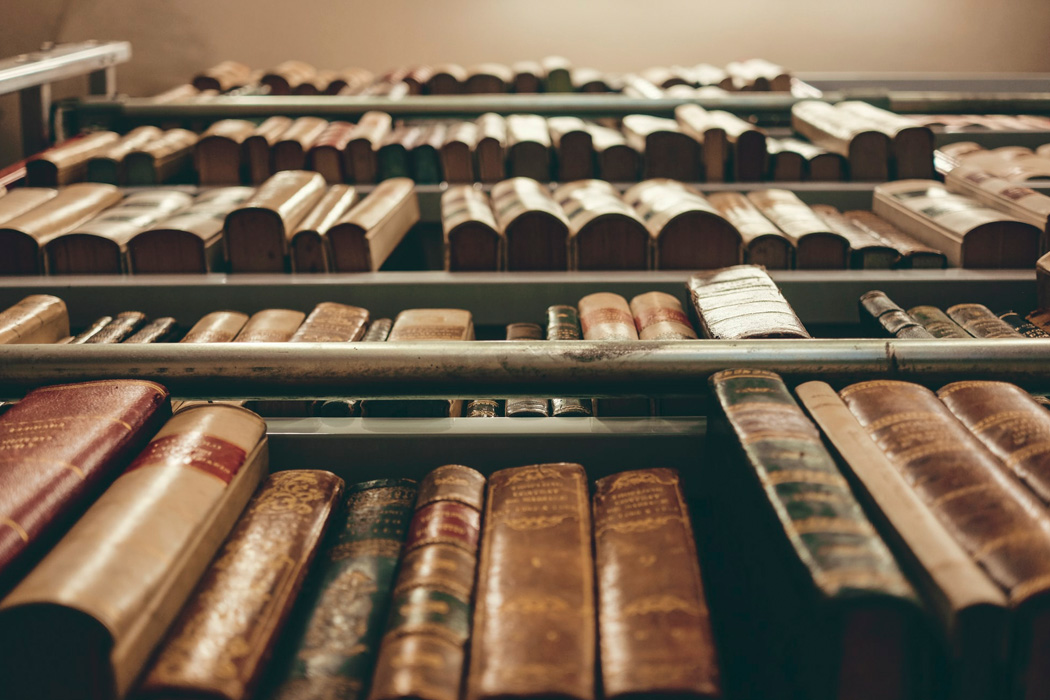 A tall bookcase of old books
