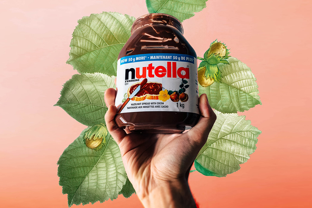 A hand holding a jar of Nutella in front of an illustrated hazelnut plant