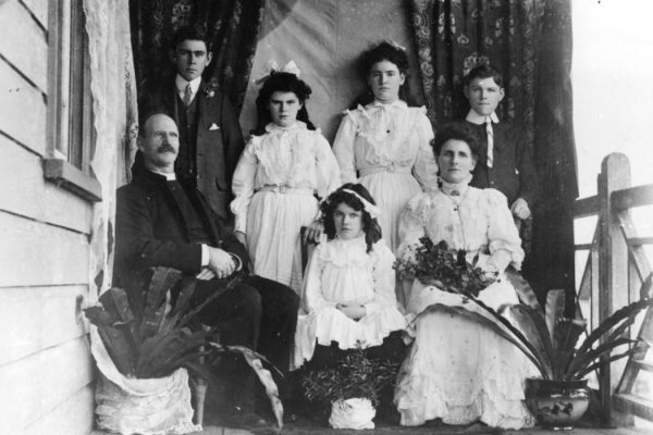 A family poses for a portrait in front of a fabric backdrop on the veranda of their home, in the early 1900s.