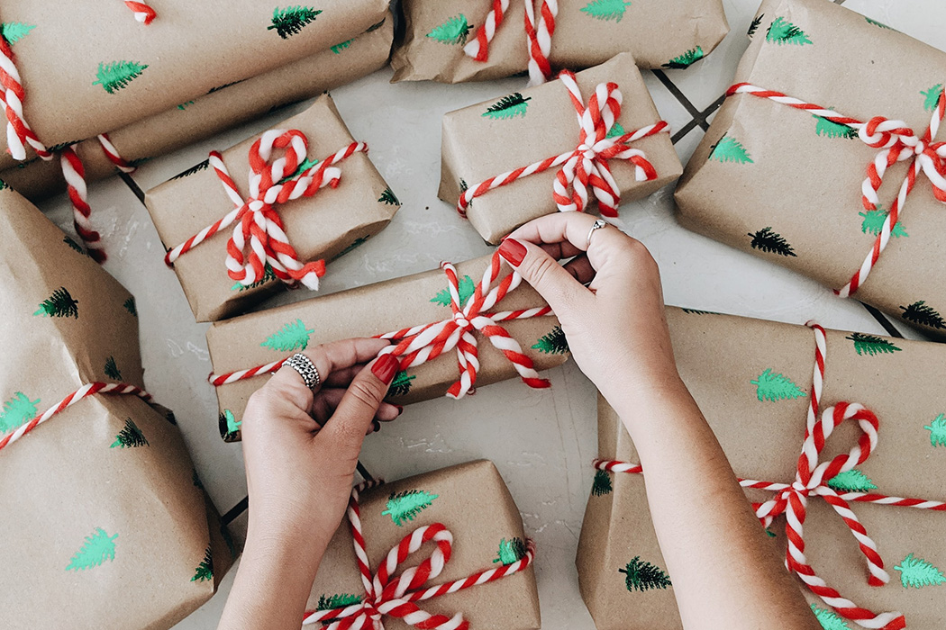 A person's hands wrapping Christmas gifts