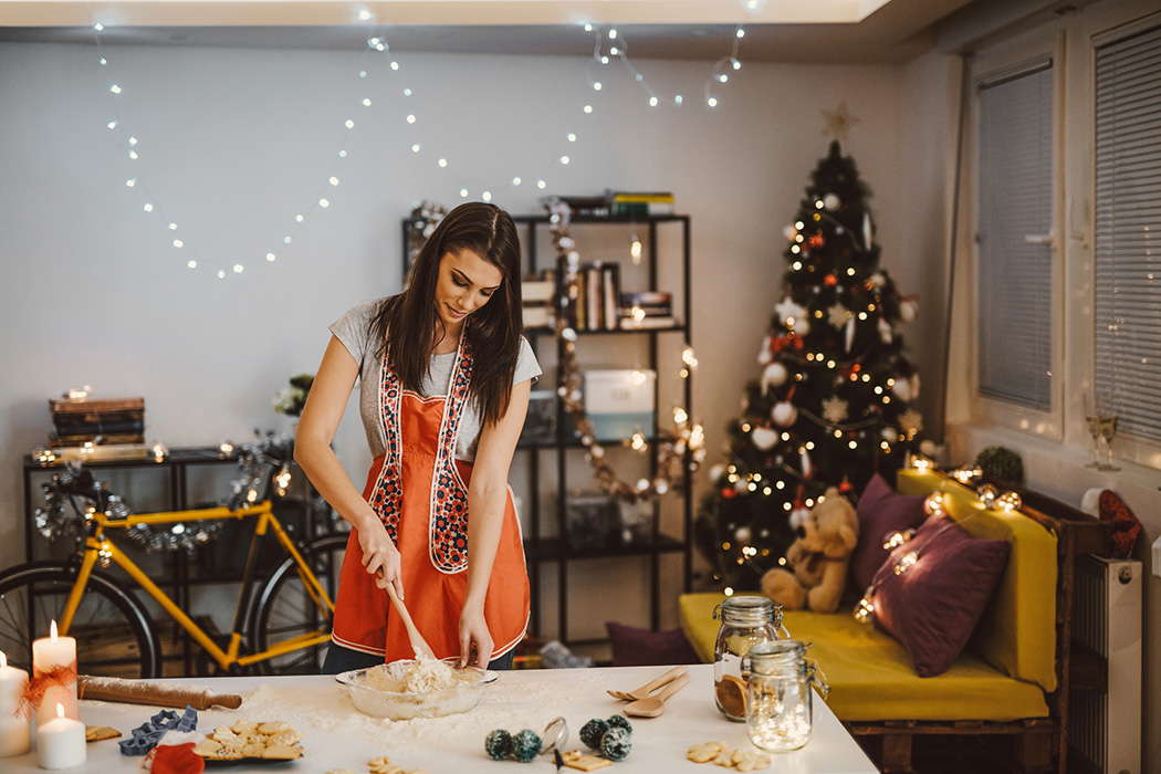 A woman in the kitchen in front of a Christmas tree