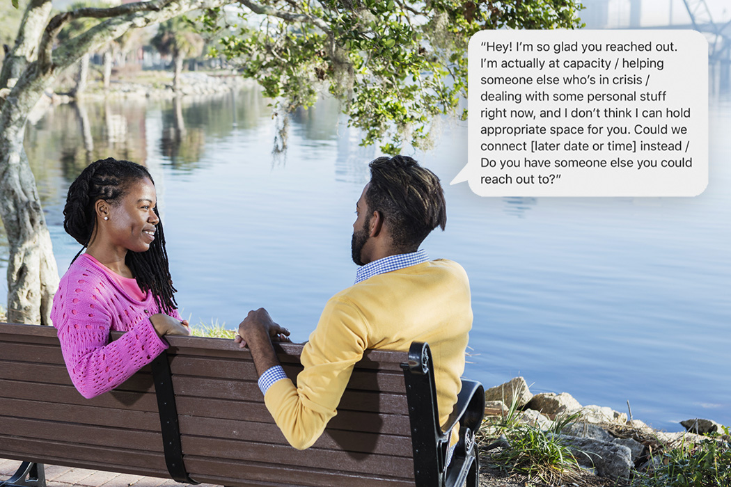 A mid adult couple in their 30s sitting on a park bench overlooking a city waterfront. The woman is African-American and the man is mixed race African-American and Hispanic. They are conversing face to face.