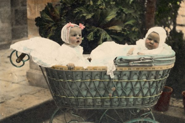 Vintage Portrait of two Babies in an Old Fashioned Antique Baby Carriage Buggy