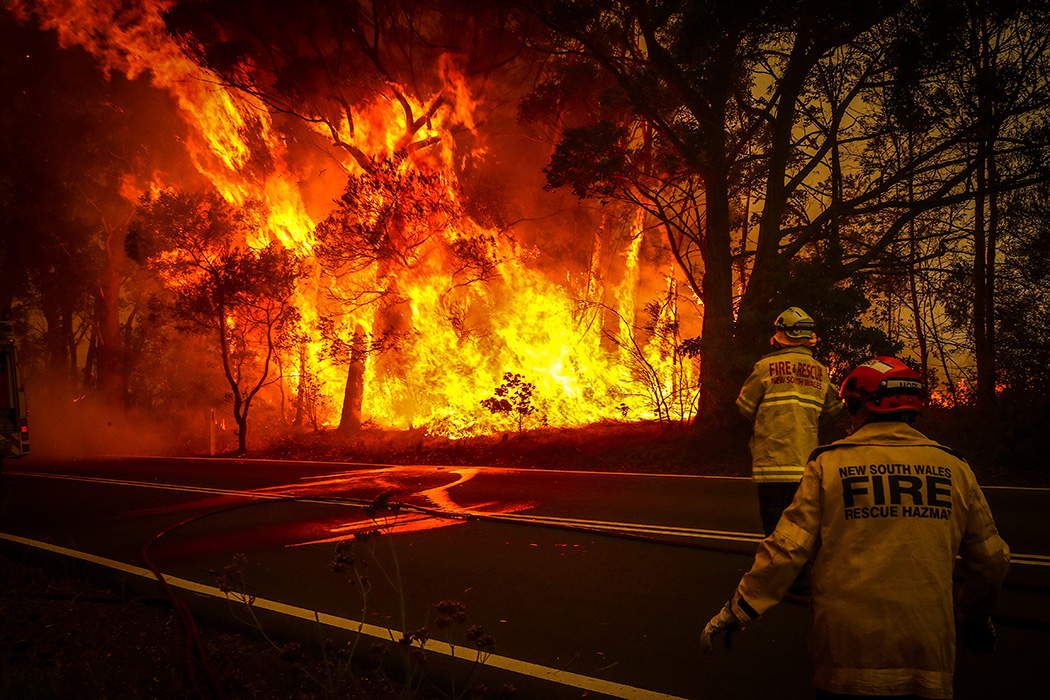 Fire and Rescue personal watch a bushfire as it burns near homes on the outskirts of the town of Bilpin on December 19, 2019 in Sydney, Australia.