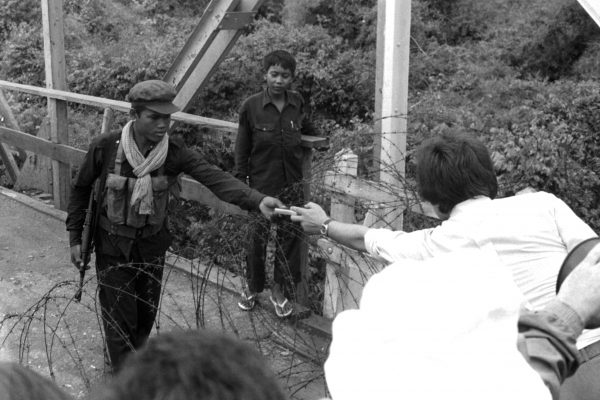 Khmer Rouge guerilla accepts a gift of cigarettes from a waiting French official, May, 1975.