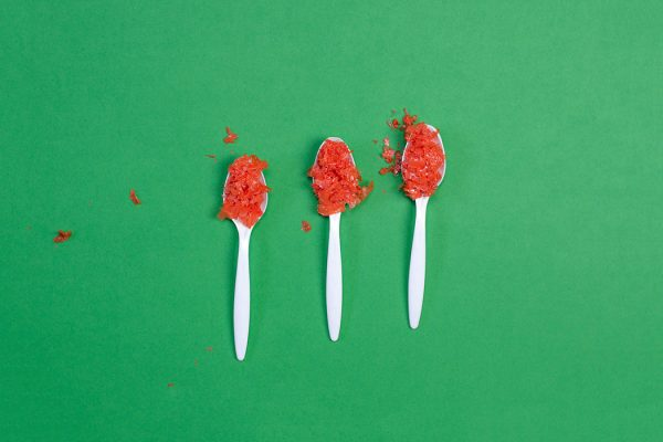 Three spoonfuls of red microplastic on a green background.