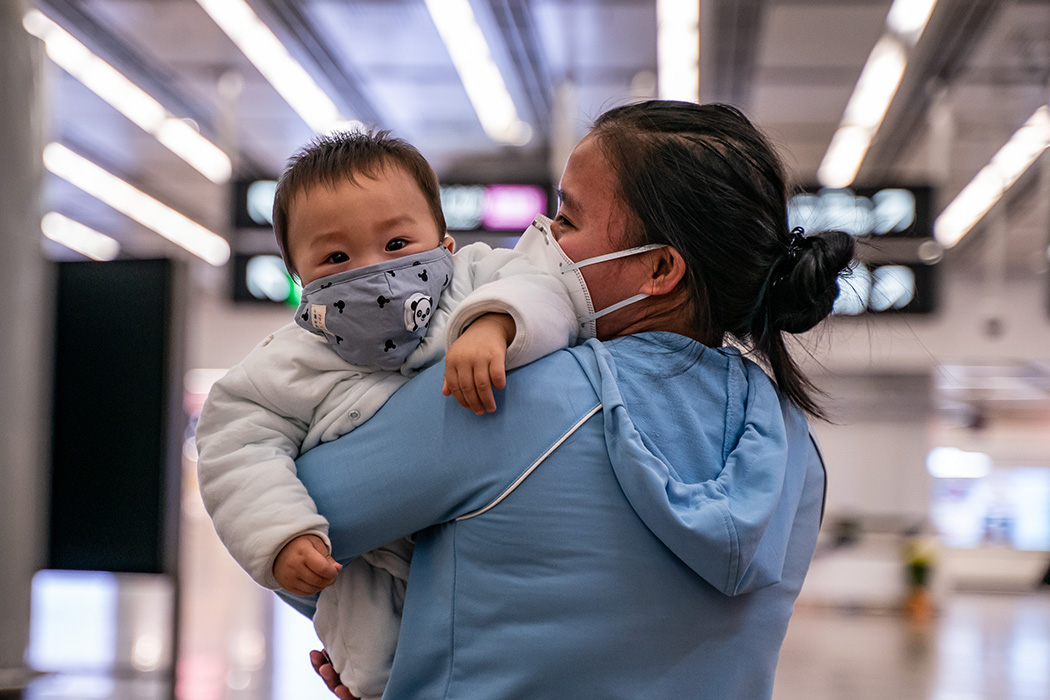 A woman carries a baby wearing a protective mask as they exit the arrival hall at Hong Kong High Speed Rail Station on January 29, 2020 in Hong Kong, China.