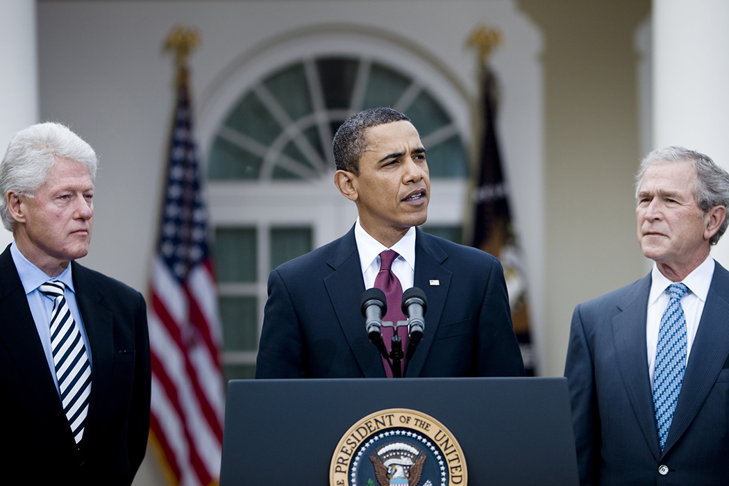 President Barack Obama speaks as former President Bill Clinton (L) and former President George W. Bush (R) listen in the Rose Garden of the White House January 16, 2010. President Obama and the former Presidents Bush and Clinton spoke about the efforts to coordinate American Charitable aid to the earthquake victims in Haiti.