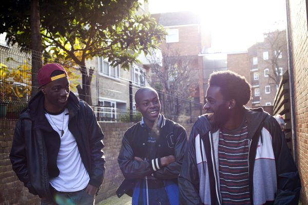 3 boys hanging out outside laughing