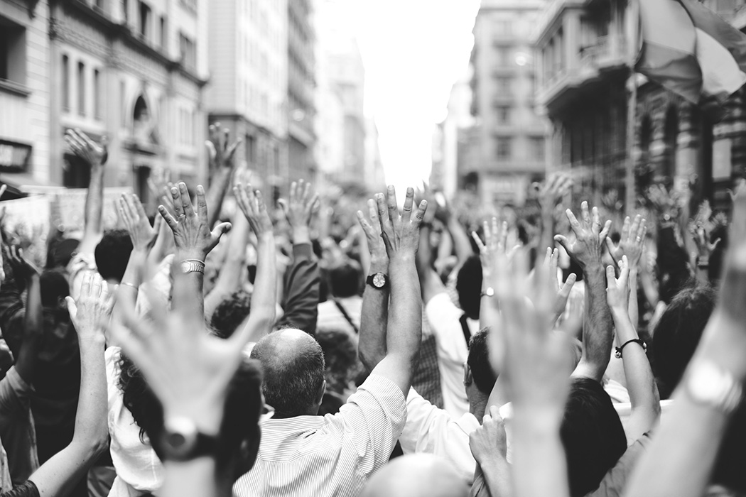 Peoples with hands raised gathered on street.