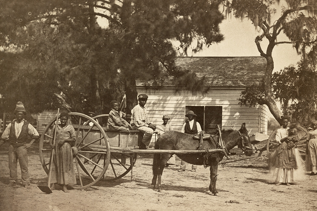 a group of African American slaves posed around a horse-drawn cart, with a building in the background, at the Cassina Point plantation of James Hopkinson on Edisto Island, South Carolina.