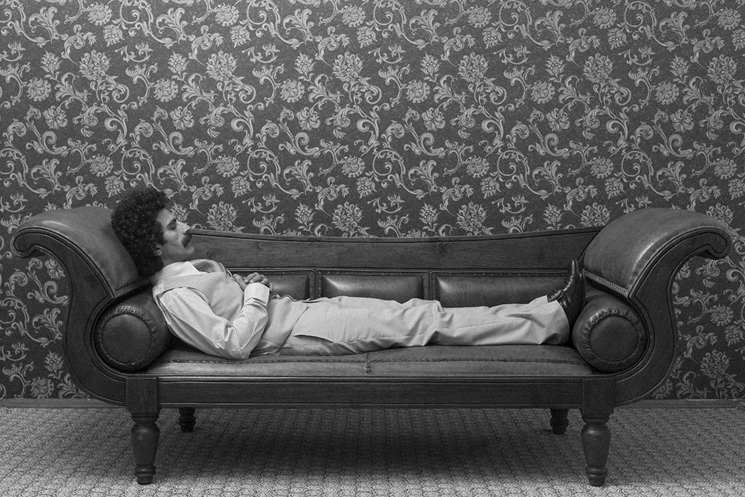 A man lying down on a couch in a psychiatrist office.