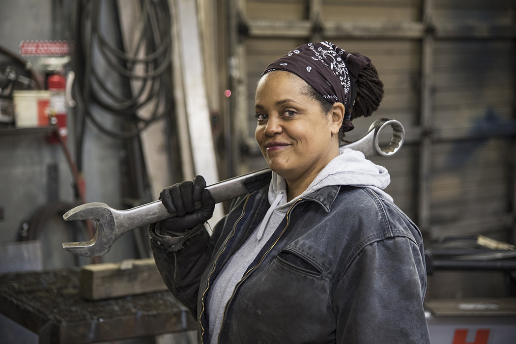 An African American worker carrying a tool in a factory