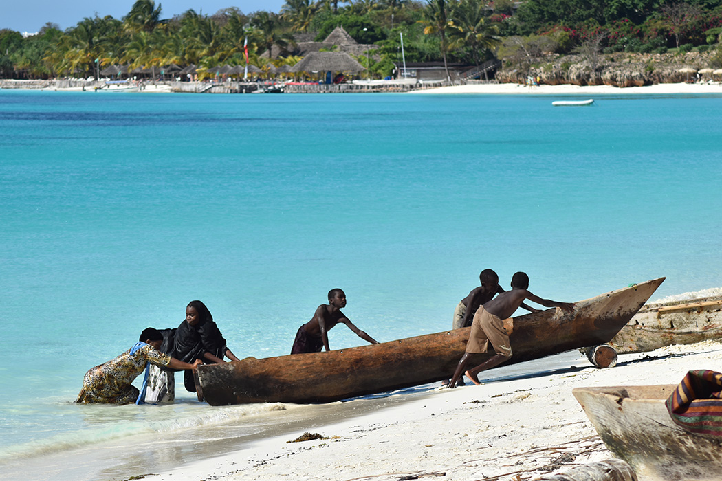 Children push a fishing boat to shore in Zanzibar